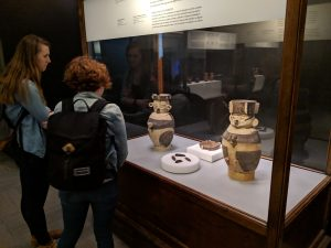 Two members, Izzy and Lily, looking at pottery in a glass display case in the mummification exhibit