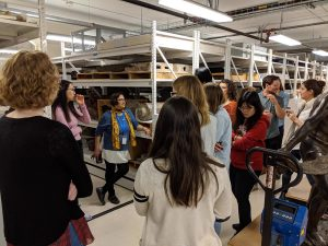 Dr. Wali leaning on a metal shelving unit talking to a group of members in the Field Museum's anthropological collection