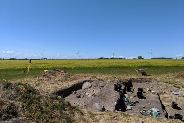 Excavation pit with equipment in the foreground, with a wheat field, windmills, and cloudless blue sky behind it