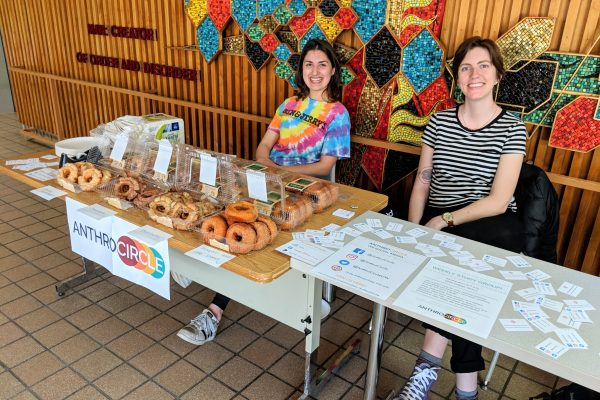 Megan and Delaney sitting behind tables in the Social Sciences lobby at our spring donut fundraiser